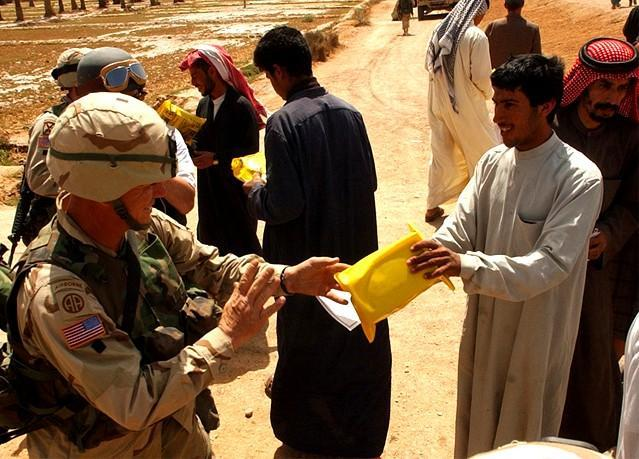 Staff Sgt. Joseph Cole, headquarters commandant, HHC 82nd Airborne Division, hands a humantarian ration to a young Iraqi man near As Samawan. (U.S. Army photo by Staff Sgt. Eric Foltz, 49th PAD)