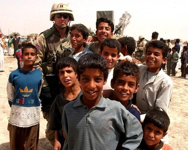 Capt. Jimmie Cummings, commander, 49th Public Affairs Detachment, 82nd Airborne Division is surrounded by children during a humanitarian assistance mission outside As Samawan in central Iraq. (U.S. Army photo by Staff Sgt. Eric Foltz, 49th PAD)