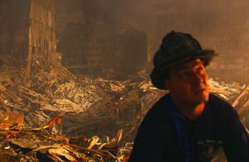 New York, NY, September 19, 2001 -- A New York Fire Department worker takes a break amidst the piles of rubble at the World Trade Center. Photo by Andrea Booher/ FEMA News Photo