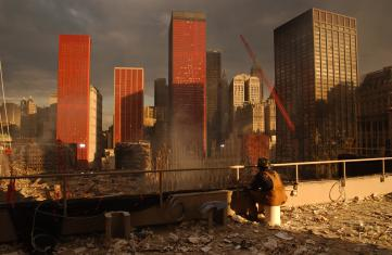 New York, NY, September 28, 2001 -- Firefighter watches debris removal at the World Trade Center from nearby roof. Photo by Andrea Booher/ FEMA News Photo