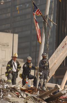 New York, NY, September 18, 2001-- New York City firefighters take a break amidst the rubble of the World Trade Center. Photo by Andrea Booher/FEMA News Photo