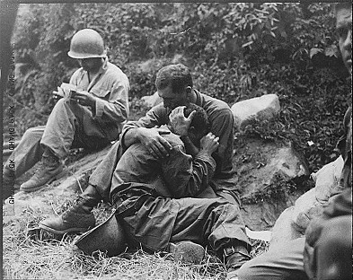 A grief stricken American infantryman whose buddy has been killed in action is comforted by another soldier.  In the background a corpsman methodically fills out casualty tags, Haktong-ni area, Korea.  August 28, 1950.  Sfc. Al Chang. (Army) Photo Source - National Archives