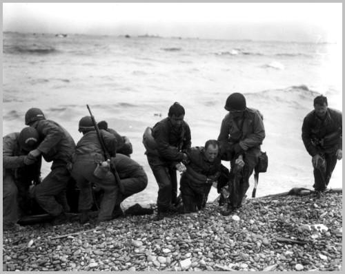Members of an American landing party lend helping hands to other members of their organization whose landing craft was sunk by enemy action off the coast of France. These survivors reached Omaha Beach, near Cherbourg, by using a life raft. Photographer: Weintraub, 6 June 1944 Photo Source: http://www.army.mil/